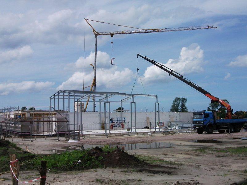 Mitarbeiter der Stahlbaufirma sind dabei das Grundgerüst der Fahrzeughalle herzustellen.   Bild: Meyer